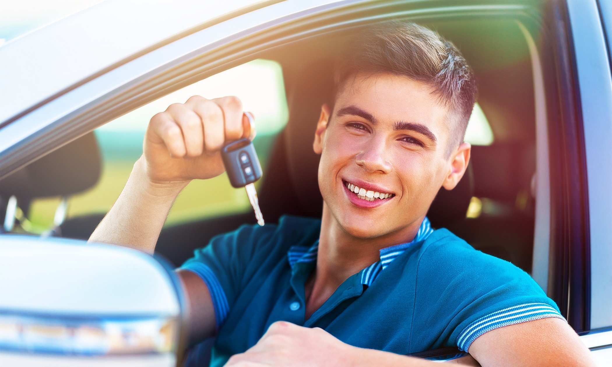 young happy man with keys in car